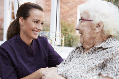 female caregiver assisting senior woman while looking at each other