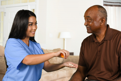 female caregiver giving medicine to senior man