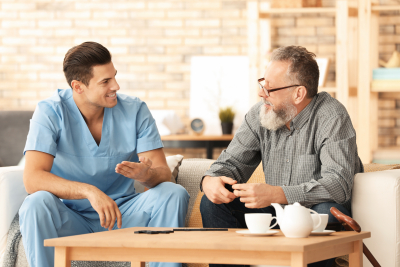 male caregiver and senior man looking at each other